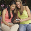 Two young women reviewing digital photos — Stock Photo #13236175