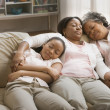 Three generations of African women sleeping on sofa - Stockfoto