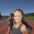 Two female track athletes training outdoors — Stock Photo