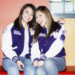 Portrait of two teenage girls wearing letterman's jackets — Stock Photo