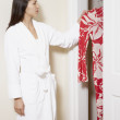 Stock Photo: Side view of woman in robe looking through closet