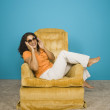 Foto Stock: Portrait of womwearing sunglasses lounging in chair