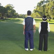 Rear view of couple on golf course - Stock Photo