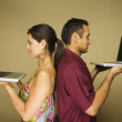 Hispanic couple standing back to back holding laptops — Stock Photo