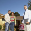 Stock Photo: Portrait of couple with realtor at open house