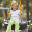 Portrait of girl swinging on tire swing — Stock Photo