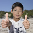 Young boy making thumbs up sign — Stock Photo