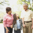Hispanic grandparents and granddaughter holding hands outdoors — Stock Photo #13236359