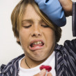 Sick boy being given cough syrup - Stock Photo