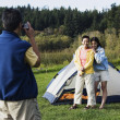 Stock Photo: Man taking picture of his family posing in front of tent