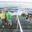 Father and son chatting on seaside steps — Stock Photo