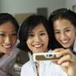 Asian businesswomen taking own photograph — Stock Photo #13236436