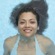 Hispanic woman floating in swimming pool - Stock Photo