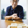Senior man playing dominos — Stock Photo #13236449