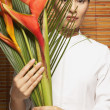 Portrait of woman holding bird of paradise — Stock Photo