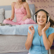 Hispanic sisters listening to music on headphones — Stockfoto