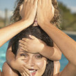 Mother carrying daughter on shoulders in swimming pool — Stock Photo