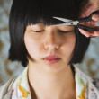 Asian woman having bangs trimmed — Stock Photo