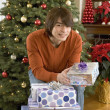 Man with wrapped gifts by Christmas tree — Stock Photo