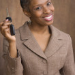Businesswoman holding up car keys — Stock Photo