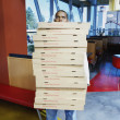 Teenage boy carrying stack of pizza boxes — Stock Photo