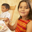 Young Hispanic girl at dinner table — Stock Photo