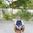 Young boy sitting on basketball — Stock Photo #13236645