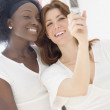 Two women taking photograph with cell phone — Stock Photo