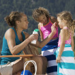 Stock Photo: Mother applying suntan lotion to daughters at beach