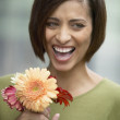 Young laughing woman holding flowers — Stock Photo #13236754