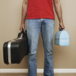 Low section of man carrying lunchbox and guitar — Stock Photo