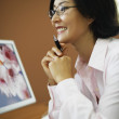 Portrait of Asian businesswoman at desk — Stock Photo