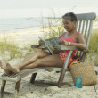 Senior woman reading on beach in lounge chair — Foto Stock