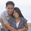 Asian couple hugging and smiling at beach — Stock Photo