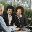 Businessman talking to couple in office — Stock Photo