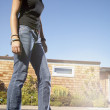 Low angle portrait of teenage girl on skateboard — Stock Photo