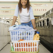 Portrait of womwith baskets of clothes in laundromat — Stock Photo #13236823