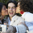 Man taking photograph of two women kissing him — Stock Photo