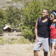 Stockfoto: AfricAmericcouple with backpacks hugging outdoors
