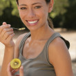 Young woman eating kiwi — Stockfoto