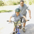 African American father helping son ride bicycle — Stock Photo