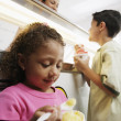 Brother and sister eating ice cream in ice cream shop - Stock Photo