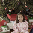 Hispanic girl surrounded by Christmas gifts — Foto Stock