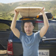 Man lifting surfboard from car rack — Stock Photo