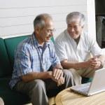 Two elderly men sitting with laptop — Stock Photo