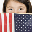 Close up of Asian girl holding American flag in front of face — Stock Photo #13236900