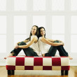 Two young women sitting back to back — Stock Photo #13236926