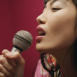 Profile of woman with microphone singing — Stock Photo