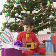 Stock Photo: Little boy opening his Christmas gift