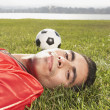 Portrait of man laying in grass with soccer ball — Stock Photo